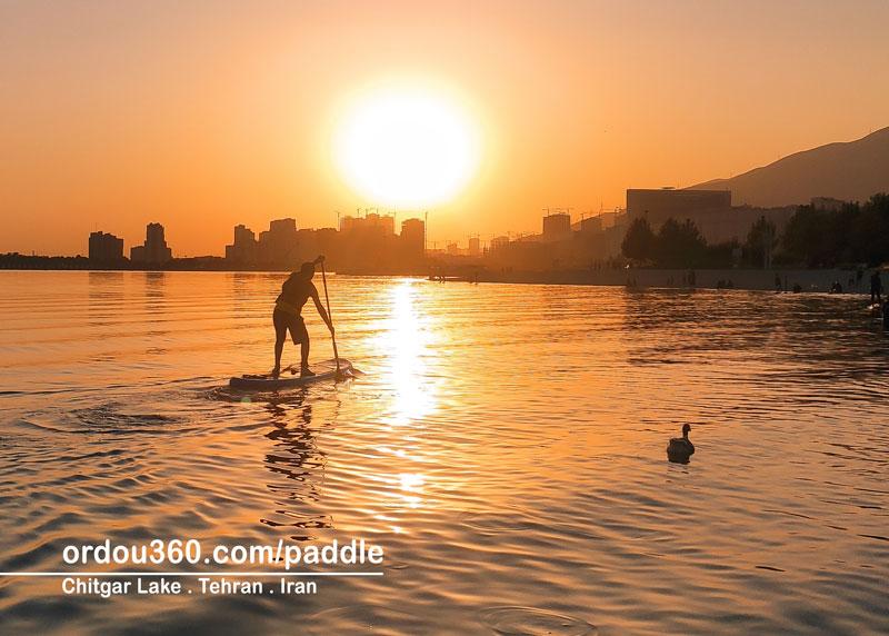 یک ورزشکار در حال استفاده از پدل برد در دریاچه چیتگر تهران
